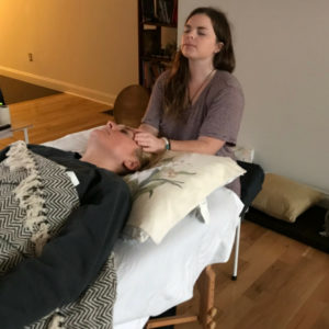 student giving reiki in class
